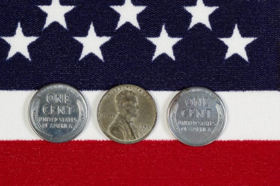 Closeup view of United States One Cent Pieces, original World War II dates, placed on American Flag