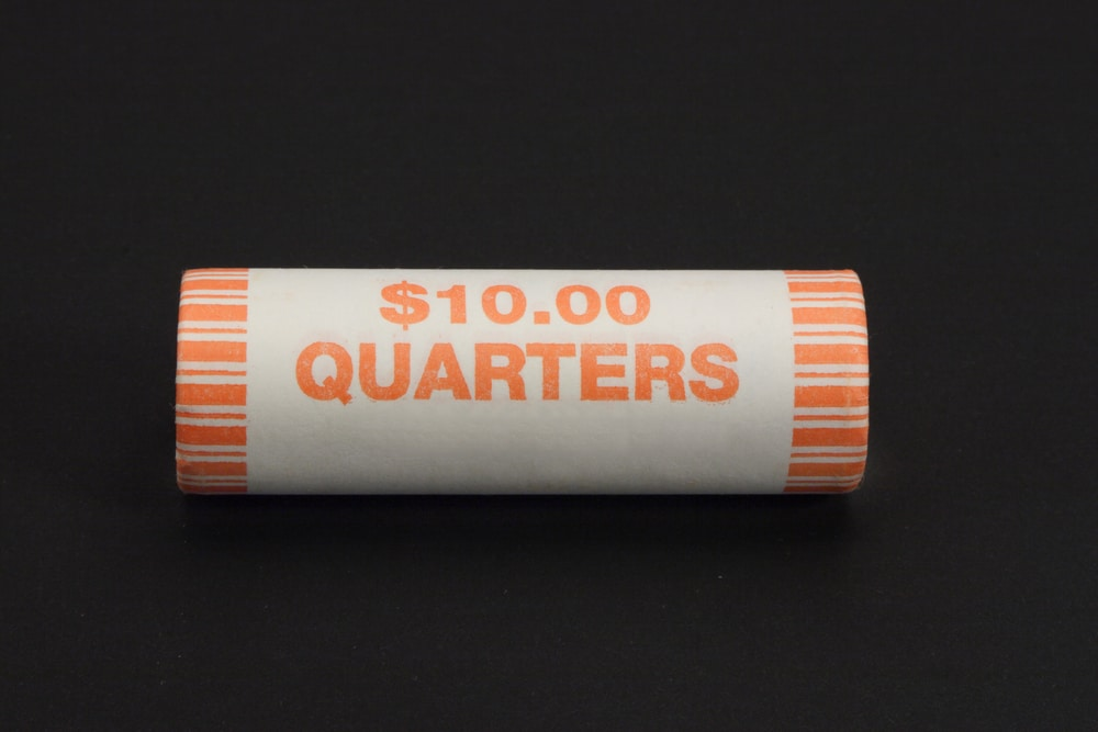 Roll of quarters on black background